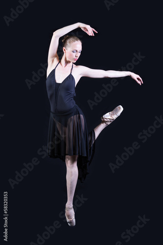 Ballet dancer in black dress isolated on gray background