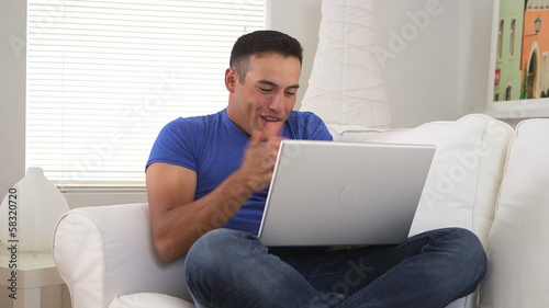 Disappointed Hispanic man watching sports on laptop computer