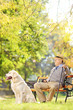 Senior gentleman seated on bench with dog relaxing in a park