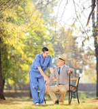 Healthcare professional talking senior man seated on bench