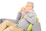 Mature man seated on a sofa taking asthma treatment with inhaler