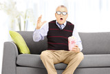 Shocked senior man with popcorn sitting on sofa and watching