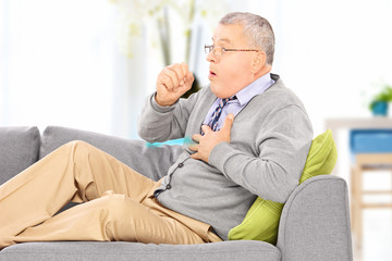 Mature man seated on a sofa coughing at home