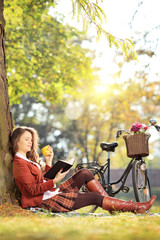 Young female reading book and eating apple, on a sunny day
