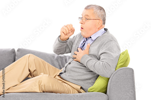 Mature man seated on a sofa coughing