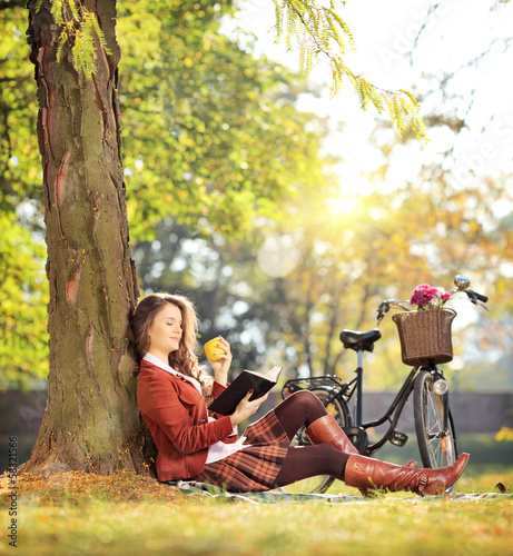 Young beautiful female in park reading a book and eating apple