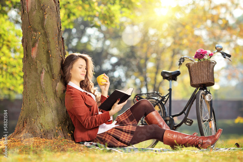 Young female in park reading a book and eating on a sunny day