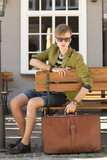Young handsome man with suitcase waits on bench