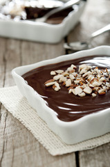 Closeup of chocolate pudding desserts sprinkled with almonds.