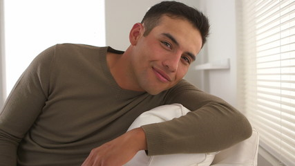 Latino man smiling and looking out window then turning to camera