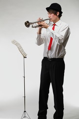 Portrait of a young man playing on his trumpet