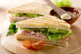 two panini sandwiches with turkey, cheese and lettuce.