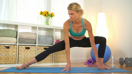 Healthy blonde woman stretching legs during workout