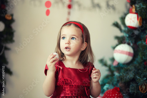 girl in a celebratory dress near Christmas tree