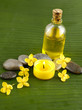 yellow flower and stones with massage oil on green banana leaf
