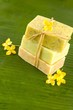 Stacked natural soaps with yellow flower on banana leaf