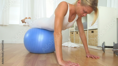 Healthy blonde woman doing push ups with balance ball
