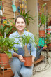 woman with Nolina plant in pot at flower store