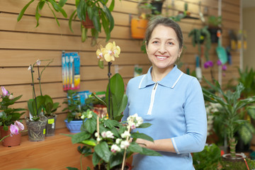 Happy  woman with Phalaenopsis in pot