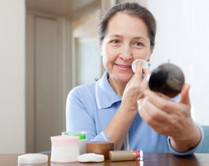 Mature woman cleans the make-up