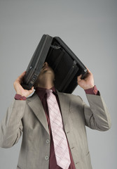 Businessman holding a briefcase over his head