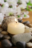 still life a lit candle and stones on wooden background
