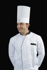 Chef standing with hands behind back and smiling