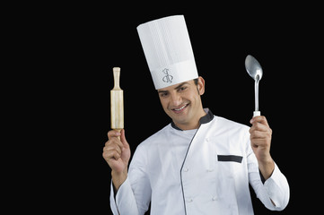 Chef holding a rolling pin and a ladle