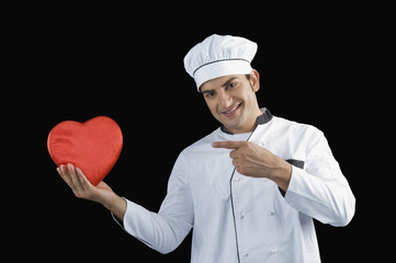 Chef pointing towards a heart shape gift