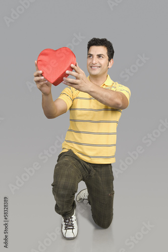Man proposing with a heart shape gift