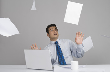 Businessman sitting in office with papers falling around him