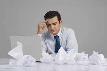 Businessman looking worried with crumpled papers on desk