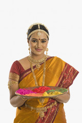 South Indian woman holding a tray of powder paints for rangoli