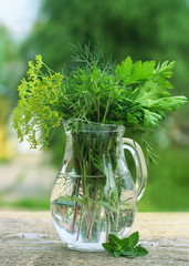 Jug with fresh parsley, fennel, basil on an old wooden table