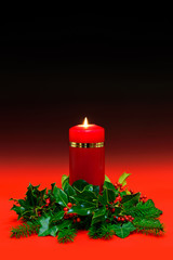 Christmas candle with holly and ivy on red background.