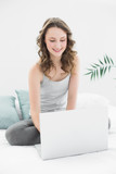 Smiling casual young brunette using laptop in bed