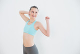 Smiling toned woman stretching hands against wall