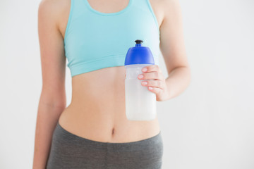 Mid section of fit woman holding water bottle against wall