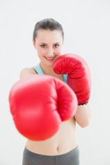 Portrait of a smiling woman in red boxing gloves