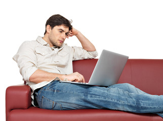 resting man with laptop sits on the divan