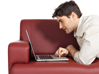 smiling happy man with laptop on the divan