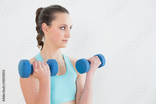Serious woman with dumbbells against wall