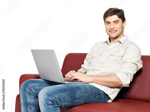 smiling happy man with laptop sits on the divan