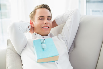 Portrait of a relaxed young man with book lying on sofa