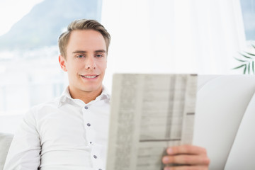 Smiling relaxed man reading newspaper on sofa