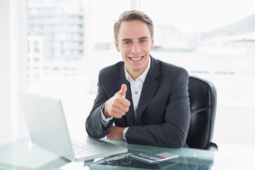 Businessman with laptop gesturing thumbs up at office desk
