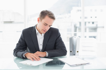 Businessman reading documents at office desk