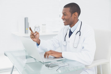 Smiling male doctor text messaging while using laptop