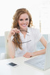 Smiling businesswoman with laptop at desk in office