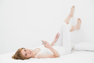 Portrait of relaxed woman with mobile phone in bed